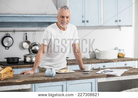Take Care. Happy Male Person Keeping Smile On His Face And Leaning On Table While Preparing Dinner
