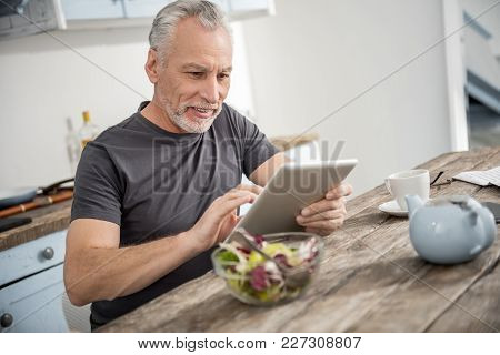 Modern Technologies. Handsome Bearded Man Keeping Smile On His Face And Looking At His Gadget While