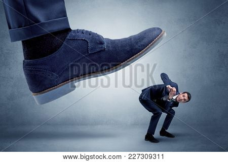 Big foot trying to crush small man who is afraid of that