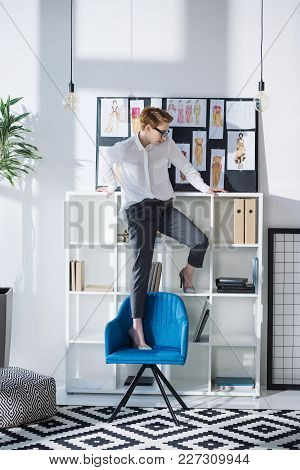 Stylish Attractive Fashion Designer Standing On Chair At Office