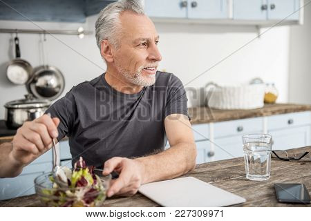 Dinner Preparation. Happy Bearded Male Person Keeping Smile On His Face And Turning Head While Mixin