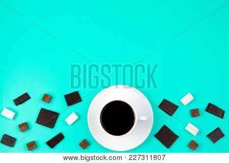 White Cup Of Coffee, Brown And White Sugar Cubes And Chocolate Pieces On Turquoise Background. Top V