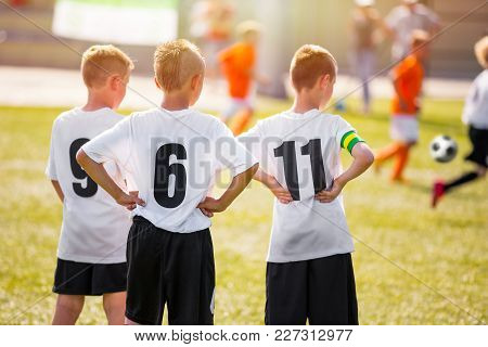 Kids Soccer Team Players Standing On Grass Pitch On A Sunny Day. Young Boys Watching Soccer Match. Y