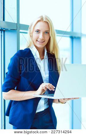 Businesswoman standing against office window holding laptop. Businesswoman