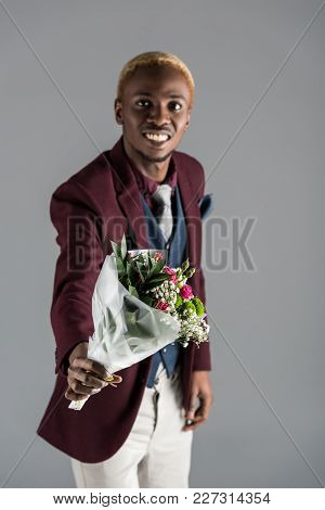 Smiling African American Man In Jacket With Bouquet In Hand Isolated On Grey