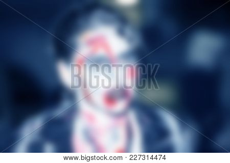 Abstract Blurred Background. People Dressed As A Zombie Parades On A Street During A Zombie Walk