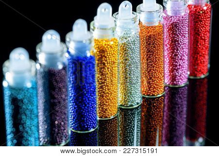 Multi-colored Beads For For Nail Design Close-up On A Black Mirror Background