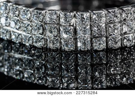 Silver Bracelet With Diamonds Close-up On A Black Mirror Background