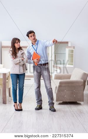 Salesman explaining to woman customer at furniture store