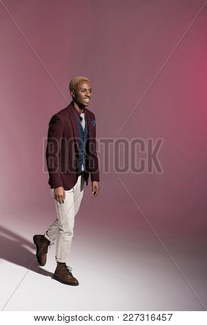 Smiling African Man In Red Jacket Walking  On Pink Background