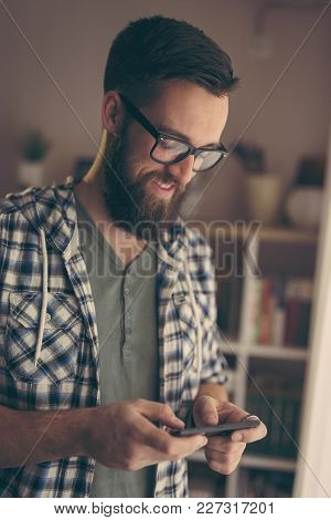Young Freelancer Working In His Home Office, Using A Mobile Phone