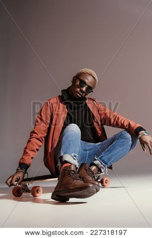 Stylish Young African American Skater Sitting On Longboard
