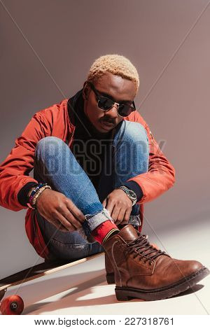 Stylish Young African American Skater Sits On Longboard And Straightens His Jeans