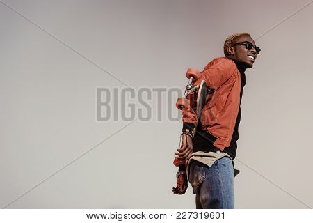Stylish Young African American Skater Holding Longboard Behind His Back Isolated On Light Background