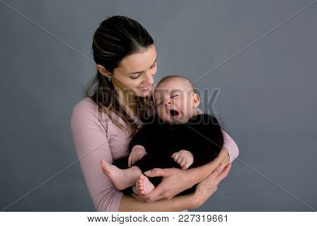 Young Mother, Caressing Her Newborn Baby Boy, Holding Him In Her Arms And Smiling