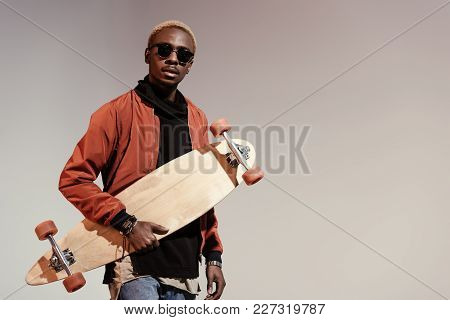 Stylish Young African American Skater Holding Longboard In Hand Isolated On Light Background