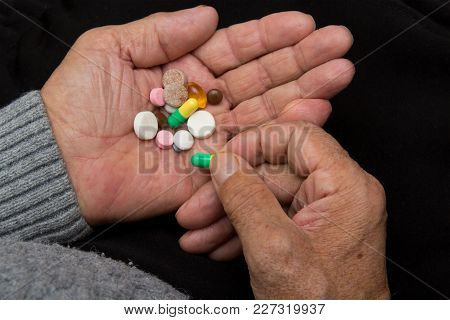 An Elderly Man Holds A Lot Of Colored Pills In Old Hands On A Dark Background.identification Of Pill
