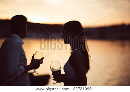 Two Young People Enjoying A Glass Of Red Wine In The Sunset On The Seaside.healthy Glass Od Homemade