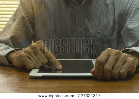 A Man Using Right Hand Touch A Tablet On Wooden Table In The Office