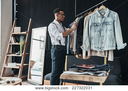 Working On New Order. Thoughtful Young Man Choosing Clothes From The Rack While Standing In The Show
