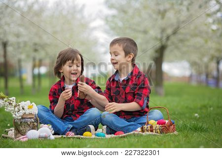 Two Children, Boy Brothers, Eating Chocolate Bunnies And Having Fun With Easter Eggs