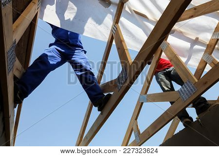 Men Building A House, Working On A Roof