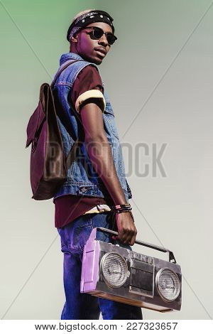 Young Handsome African American Man In Sunglasses Holding Silver Tape Recorder Isolated On Grey