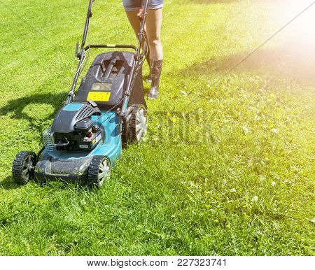 Beautiful Girl Cuts The Lawn. Mowing Lawns. Lawn Mower On Green Grass. Mower Grass Equipment. Mowing