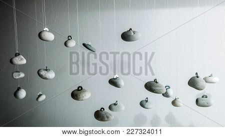 Close Up View Of Small Grey Pebbles Hanging From String