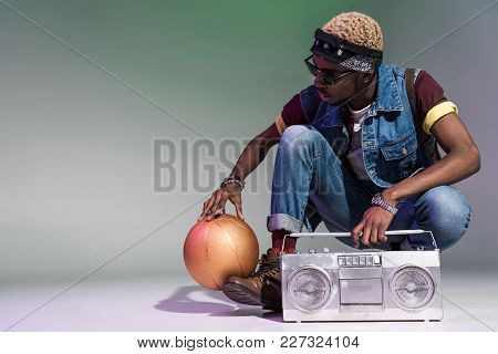 Young African American Man Crouching With Golden Basketball Ball And Silver Tape Recorder On Grey