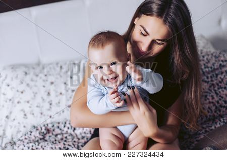 Young Mother With The Small Child Sit On A Bed And Smile