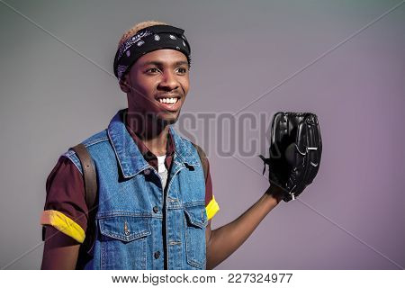 Smiling Young African American Man With Baseball Glove Looking Away Isolated On Grey
