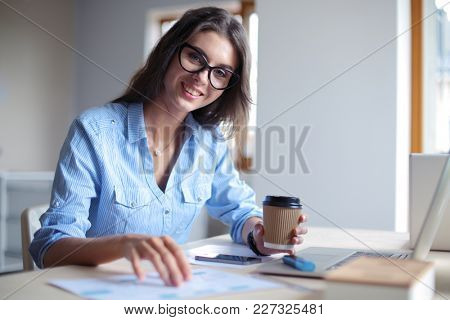 Young woman sitting in office table, looking at laptop computer screen . Young woman
