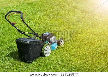 Mowing Lawns. Lawn Mower On Green Grass. Mower Grass Equipment. Mowing Gardener Care Work Tool Close