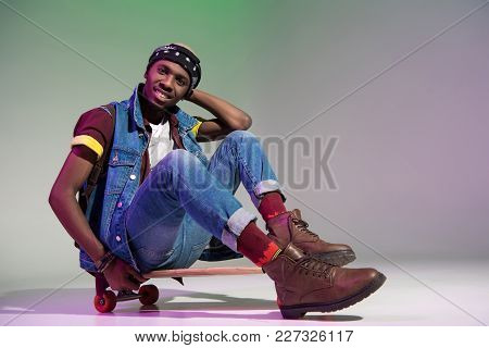 Handsome Stylish Young African American Man Sitting On Skateboard And Smiling At Camera On Grey