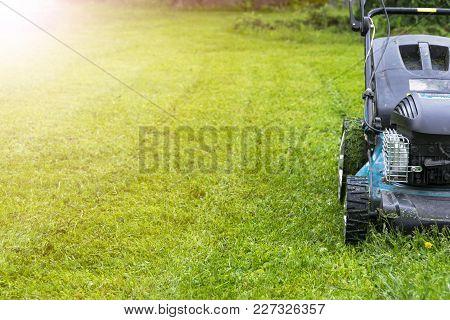 Mowing Lawns. Lawn Mower On Green Grass. Mower Grass Equipment. Mowing Gardener Care Work Tool Close