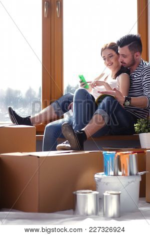 Couple moving in house sitting on the floor . Couple