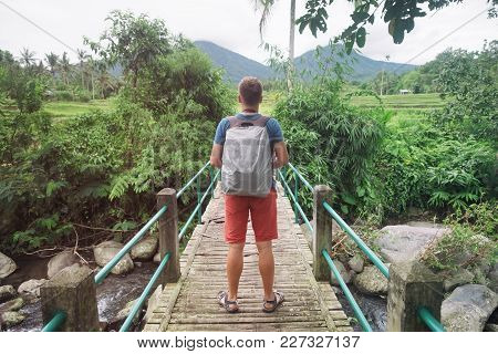 Caucasian Man Standing On Bridge And Looking Ahead. Back Side View. Concept Of Travelling In Indones
