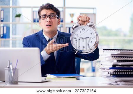 Businessman with giant clock failing to meet deadlines and missi