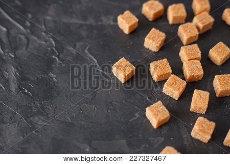 Brown Cane Sugar Cubes Pile On A Black Background. Copy Space For Text
