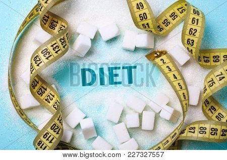 Diet Words  From Sugar On A Green Background With A Bunch Of Sugar And Yellow Measuring Tape