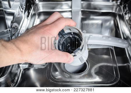 The Man Cleans The Filter In The Dishwasher.