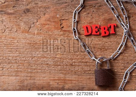 Debt Of Red Letters Near The Chain With A Closed Lock On The Wood Background. Copy Space For Text