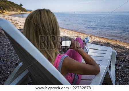Girl Sitting And Resting On A Beach Chaise Lounge And Having Fun With Her Phone. Beautiful Blue Sky