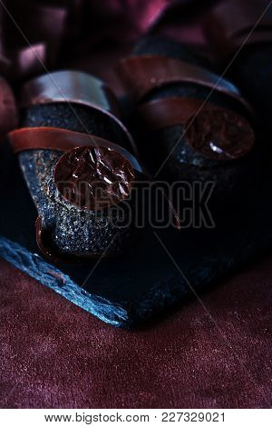 Black Chocolate Eclair With Truffle Coating On A Dark Background. An Exquisite French Dessert.