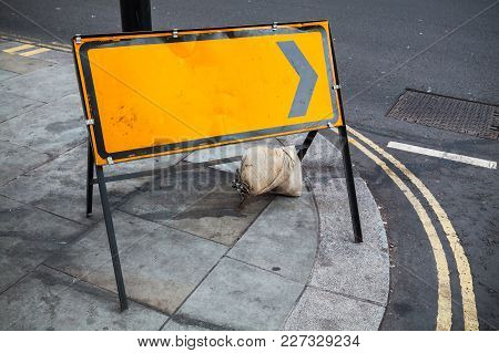 Empty Yellow Road Sign Stands On Street  Of Big City
