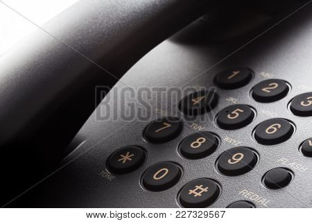 Black Phone Keypad With Yellow Numbers Closeup