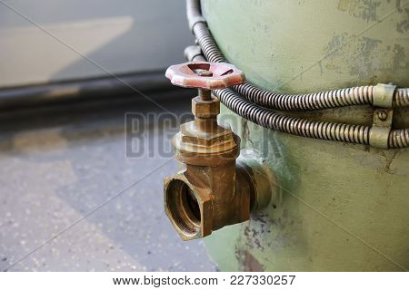 Old Brass Faucet With A Red Valve Is Screwed Into A Large Metal Container
