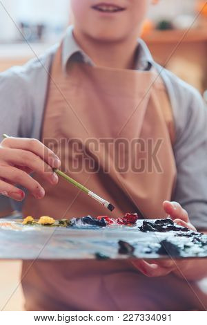 Finding A Perfect Shade. Palette With Different Bright Oil Paints And A Hand Of A Teenager Working W