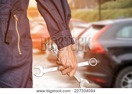 Car Repairman Wearing A Dark Blue Uniform Standing And Holding A Wrench That Is An Essential Tool Fo